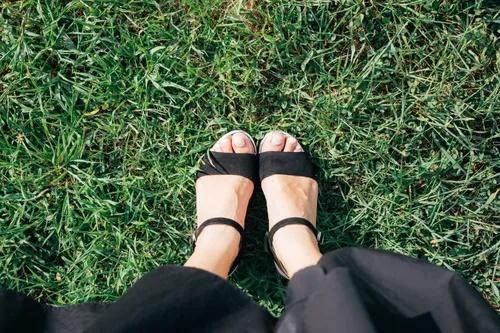 芝生に立つ女性の足元